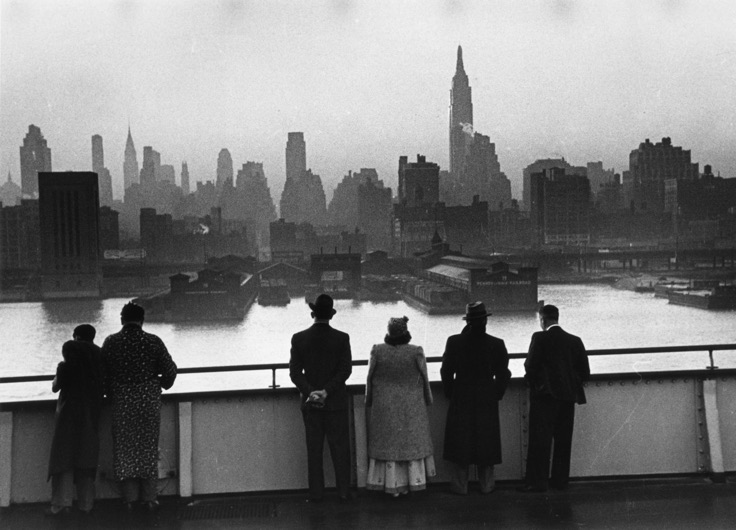 """New York Şafağı"" / ""New York Dawn"" Kurt Hutton - Picture Post - Getty Images   Orijinal yayın / Original publication: Picture Post - 198 - Atlantic Crossing Yayım tarihi / Published: 1939 Cunard White Star şirketinin yolcu gemisi Queen Mary'nin güvertesindeki yolcular, gemi şafak vakti Manhattan'da limana girerken New York silüetini seyrediyorlar, 12 Ağustos 1939."