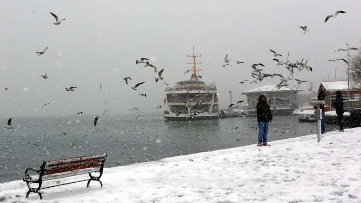 People feed seagulls by the Bosphorus during a snowfall in Istanbul