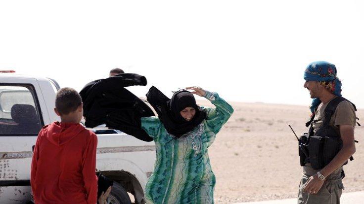 DUVAR - Suriye'nin Deyrül Zor vilayetinin doğusunda IŞİD kontrolündeki bir bölgeden kurtarılan bir kadın, ilk iş olarak örgütün zorunlu kıldığı çarşafı çıkarırken görüntülendi.